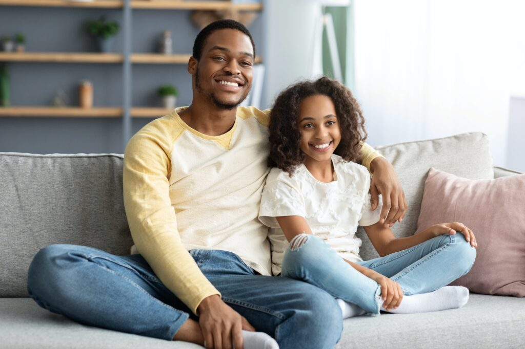 Adorable black family father and daughter watching movie together