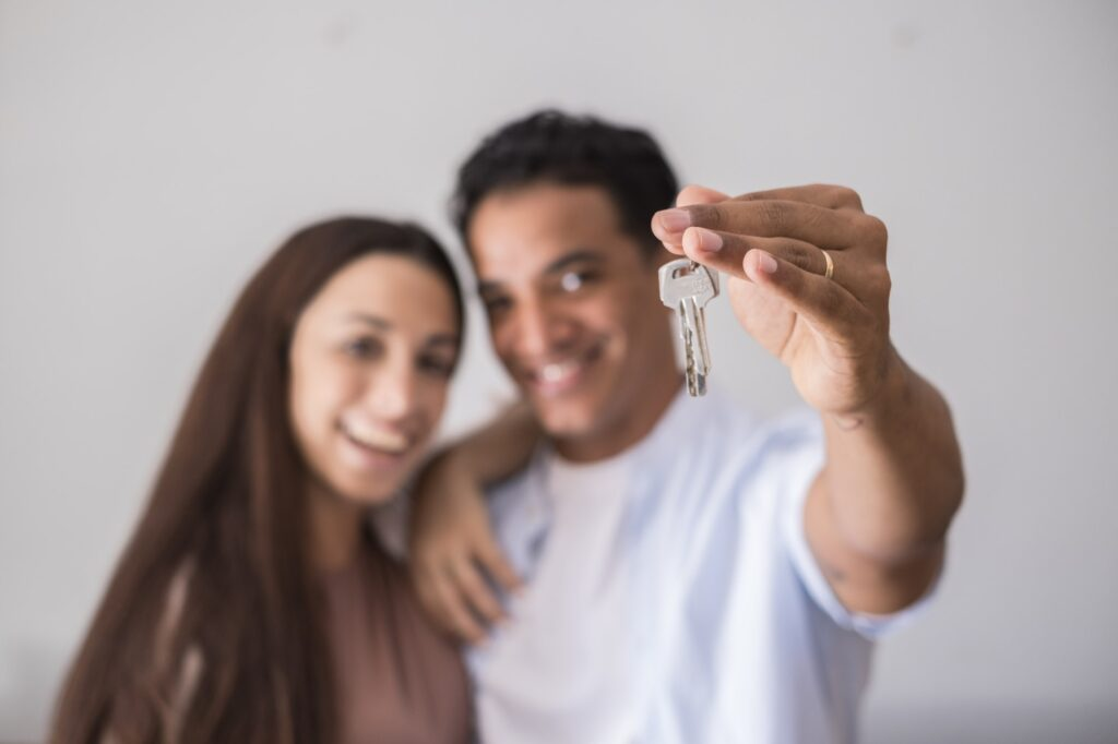 Close up of new home keys and young interracial couple smile and show the property - new life