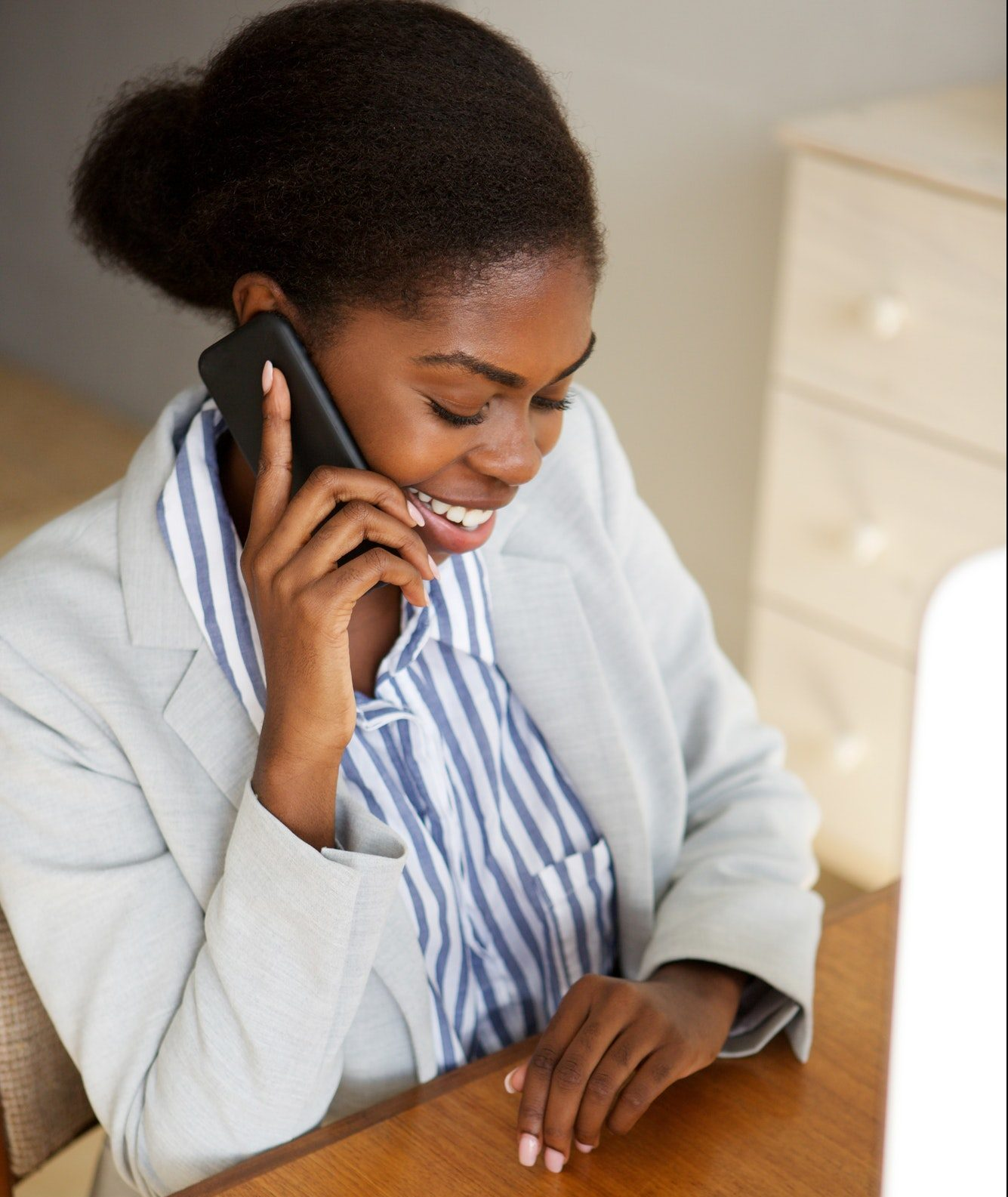 smiling young black business woman sitting in office talking on telephone