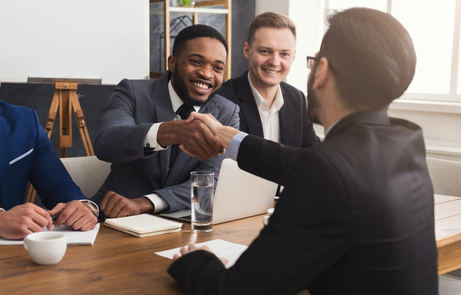 Business handshake at multiethnic office meeting